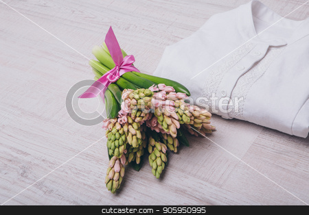 rolled up white shirt and flowers close up on white background stock photo, rolled up white shirt and flowers close up on white background by aaalll3110