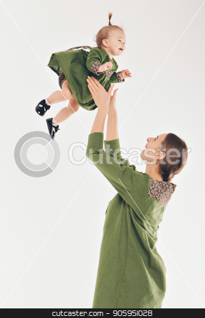 family portrait on the floor on white background. parent hold children in their arms. A woman lifted a girl up. fashion for family stock photo, family portrait on the floor on white background. parent hold children in their arms. A woman lifted a girl up. fashion for family by aaalll3110