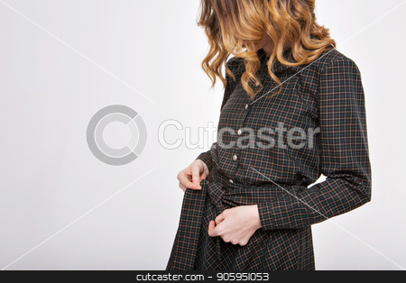 girl ties a belt on a dress. Hands on fabric background close-up. Element of clothes stock photo, girl ties a belt on a dress. Hands on fabric background close-up. Element of clothes by aaalll3110
