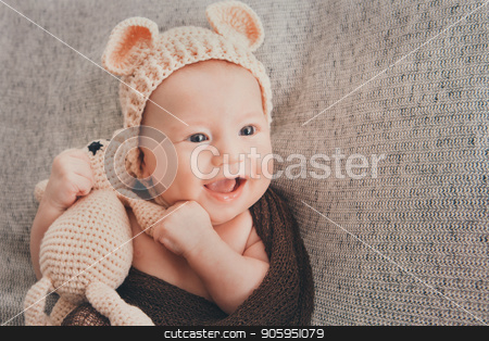 Light-eyed smiling baby. A little child in a beige cap with ears and a knitted beige toy in his hand stock photo, Light-eyed smiling baby. A little child in a beige cap with ears and a knitted beige toy in his hand by aaalll3110