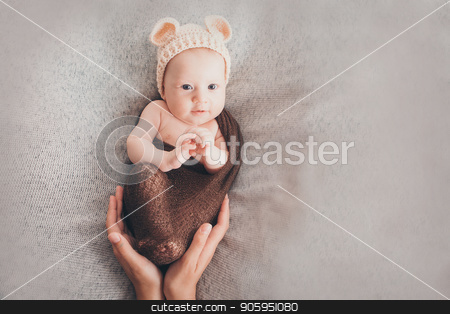 Light-eyed smiling baby. A little child in a beige cap with ears stock photo, Light-eyed smiling baby. A little child in a beige cap with ears by aaalll3110