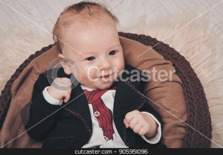 A little boy with black eyes in a business suit lies clenching his fists in a brown cradle stock photo, A little boy with black eyes in a business suit lies clenching his fists in a brown cradle by aaalll3110