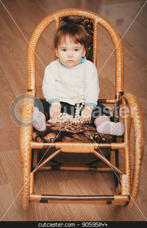 the little girl sits in a bamboo chair and plays with beads of pearls stock photo, the little girl sits in a bamboo chair and plays with beads of pearls by aaalll3110