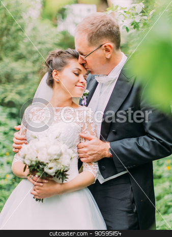 Half-length outdoor portrait of the groom kissing the bride in teh forehead in the green garden. stock photo, Half-length outdoor portrait of the groom kissing the bride in teh forehead in the green garden by Andrii Kobryn