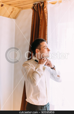 Half-length portrait of the groom tying the bow-tie while looking through the window. stock photo, Half-length portrait of the groom tying the bow-tie while looking through the window by Andrii Kobryn