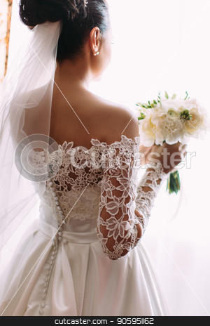 Beautiful bride is holding the wedding bouquet of white roses. The back close-up view. stock photo, Beautiful bride is holding the wedding bouquet of white roses. The back close-up view by Andrii Kobryn