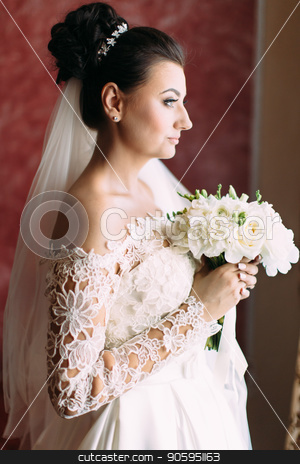 Half-length side portrait of the beautiful bride holding the wedding bouquet. stock photo, Half-length side portrait of the beautiful bride holding the wedding bouquet by Andrii Kobryn