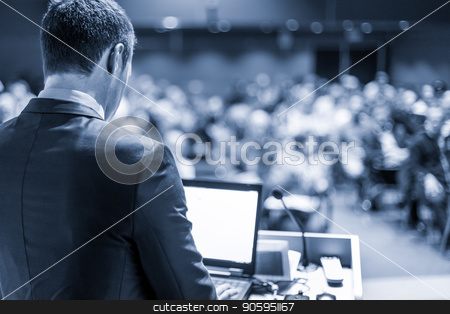 Public speaker giving talk at business event. stock photo, Speaker giving a talk on corporate business conference. Unrecognizable people in audience at conference hall. Business and Entrepreneurship event. Blue toned grayscale image. by kasto