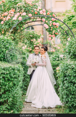 Full-length photo of the hugging newlyweds under the roses arch. stock photo, Full-length photo of the hugging newlyweds under the roses arch by Andrii Kobryn
