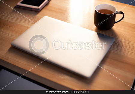 Laptop and cup of coffee or tea on the wooden table. stock photo, Laptop and cup of coffee or tea on the wooden table by Andrii Kobryn