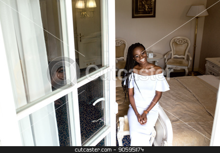 Positive beautiful afro american woman sitting in light big room in white dress in fronf of window. Positive human emotions stock photo, Positive beautiful afro american woman sitting in light big room in white dress in fronf of window. Positive human emotions by Andrii Kobryn