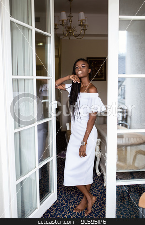 Attractive afro american woman standing in the room near the french window in beautiful long white dress. stock photo, Attractive afro american woman standing in the room near the french window in beautiful long white dress. by Andrii Kobryn