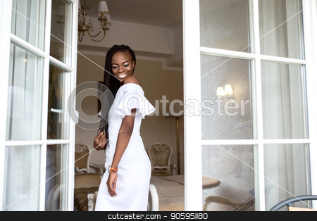 Young afro american woman with african braids or dreadlocks. Girl standing near the open glass door or french window. stock photo, Young afro american woman with african braids or dreadlocks. Girl standing near the open glass door or french window. by Andrii Kobryn