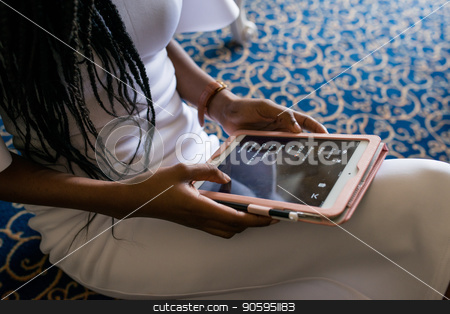 Hands of african american girl holding the tablet. Girl sitting on the floor and wearing white dress. stock photo, Hands of african american girl holding the tablet. Girl sitting on the floor and wearing white dress. by Andrii Kobryn