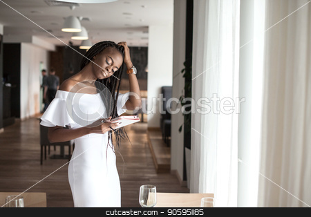 Beautiful african american girl standing near the table in a restaurant with the tablet in her hands. stock photo, Beautiful african american girl standing near the table in a restaurant with the tablet in her hands. by Andrii Kobryn