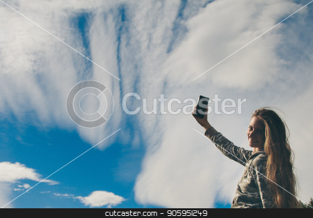 silhouette of a girl talking on the phone against the clouds. Woman posing for the camera against the sky stock photo, silhouette of a girl talking on the phone against the clouds. Woman posing for the camera against the sky by aaalll3110