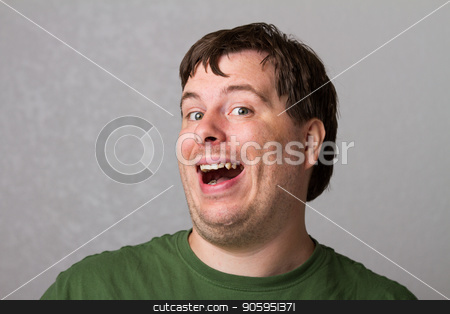 He is way too happy. stock photo, A guy smiling while looking at the camera. Smile is a little much because he is very happy. by txking