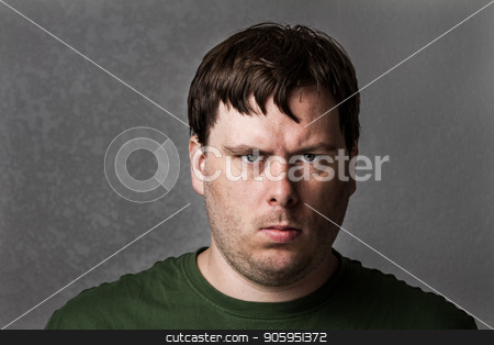 One mean looking guy about to cause problems stock photo, Male against a textured dark gray background with image slightly desaturated. the expression is angered looking. by txking