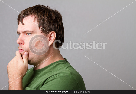 Lost in thought over a tough question stock photo, Young man thinking about something. Has a decent amount of copy space behind man. by txking