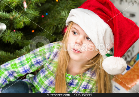 portrait of a young girl during christmas day stock photo, Girl just sitting there during christmas relaxing in front of the tree and her presents. by txking