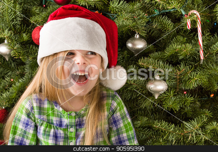 Young girl smiling wearing a santa hat stock photo, Happy young girl in front of her tree during the christmas holiday time by txking