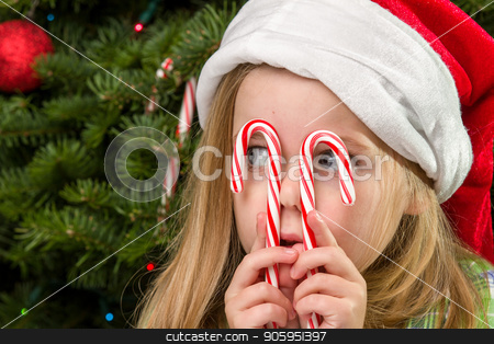 Christmas time fun stock photo, Child is holding up candy canes to her eyes making funny faces by txking