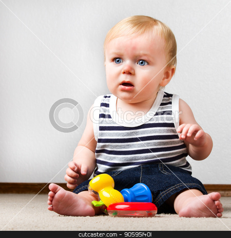 Child playing with his toys stock photo, Young toddler sitting up on the floor with a ring and a toy hammer to play with. by txking