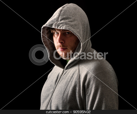 Young man in the dark of night stock photo, Man Isolated against a black background wearing a hoodie style sweater. by txking