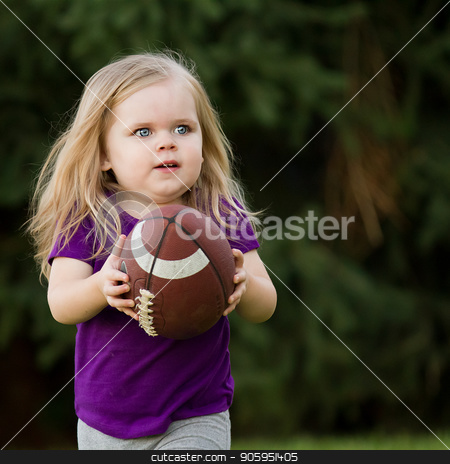 She is running for the touchdown stock photo, Young girl playing in the backyard running with her football by txking