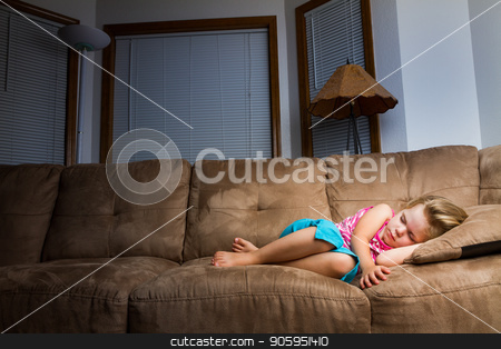 Child sleeping at night. stock photo, Child on couch curled up into a little ball at night. Nice warm light is on child that falls off as it moves away by txking