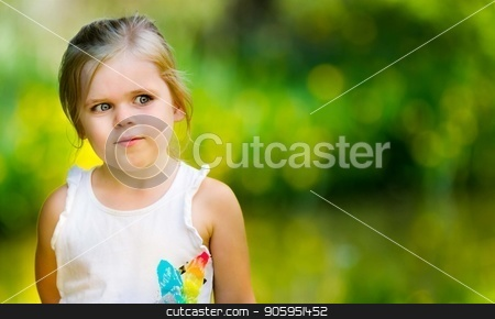 Portrait of a little girl looking into space stock photo, Young girl is against a green background with yellow highlights. lots of open copy space and girl is looking into the blank area. Image has a very shallow depth of field with focus only on the girl by txking