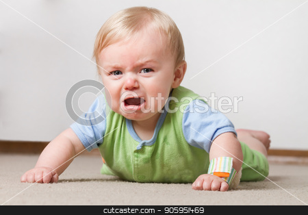 Toddler on the ground crying stock photo, A young baby having a fit on the ground crying and making a pout face by txking