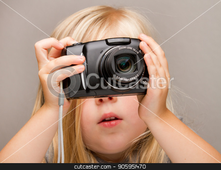Young child holding a camera taking a picture stock photo, Young child holding a point and shoot camera. Focus is on the camera as she is about to push the button by txking
