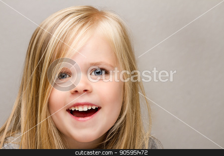Young girl with a huge smile on her face. stock photo, A Close up shot of a young girl laughing isolated against a medium gray background. by txking