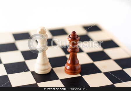 Two chess pieces on the chess board. stock photo, White King and Black queen. Can be used for multicultural, diversity,  interracial, togetherness, teamwork, or cooperation by txking