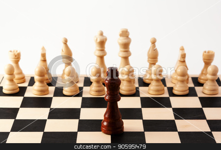 Single chess piece standing up against a collection of different pieces stock photo, Image of a single black piece standing in front of bunch of white pieces, Can be used for racism, diversity, challenge, courage, adversity, or many other uses. by txking