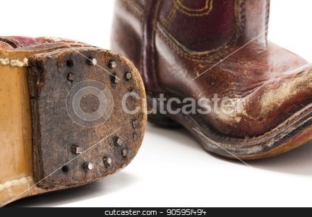 Boots from the younger years stock photo, Old worn out pare of cowboy boots from someones childhood days against a white background by txking