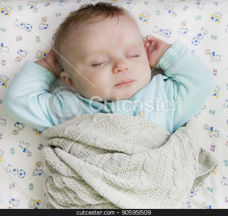 Child resting on a bed stock photo, Infant laying on his back on a bed with his hands up near his head by txking