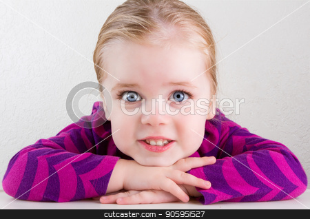 Child resting her head on her hands smiling stock photo, Single child with big bright eyes smiling straight at the camera by txking