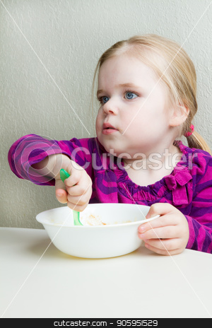 hungry little girl stock photo, Girl is sitting there eating her food as she is hungry by txking
