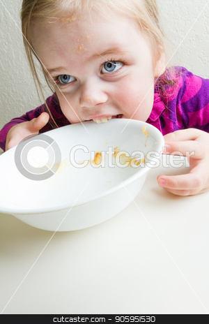 Hungry girl not given enough food. stock photo, Young girl trying to eat her bowl after not being given enough food to eat. by txking