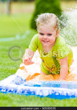 Smiling girl cooling off on a hot summer day stock photo, Young happy girl sliding down a water slide by txking