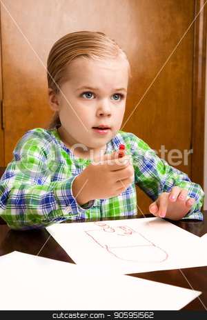 She is looking up from her masterpiece stock photo, Child at the table drawing with paper all about her.  by txking