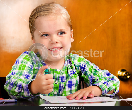Smiling young girl doing a drawing. stock photo, Child holding a crawn while drawing some pretty pictures by txking