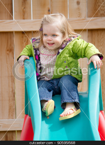 Young girl getting ready to go down the slide stock photo, A young child is enjoying her day with playing on the slide by txking