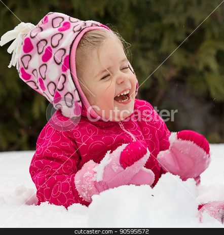 It's a cold but fun day outside stock photo, Young girl playing out in the snow during the middle of winter time. by txking