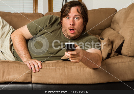 We love our shock TV stock photo, Over weight man watching something shocking on TV. Could it be tabloids, celebrity gossip, a movie, or something else?  by txking