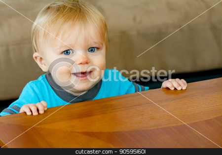 Young little boy holding himself up stock photo, Toddler against the table trying to hold himself up while learning out how to walk and making a huge smile. by txking