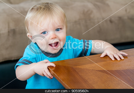 Getting ready to turn the corner stock photo, A child at the end of the table getting ready to turn the corner as he is learning how to walk. by txking