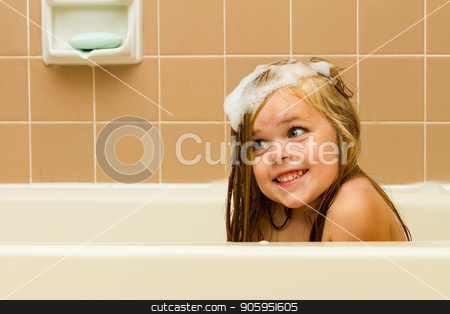 The suds of soap and a smile stock photo, Cute photo of a girl smiling with soap suds in her hair while playing in the tub. by txking